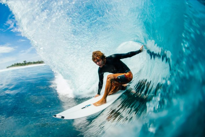 A surfer crouched on his board in the curl of a breaking wave.