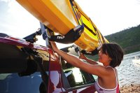 A woman loading a kayak to her roof rack using the Thule ...