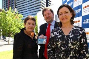 Julian Assanges australske advokat, Rob Stary, mottar nyt pressekort til Assange fra Louise Connor i det australske journalistforbundet og Ged Kearney (t.h.), leder for australsk LO (ACTU). (Foto: ACTU)
