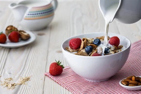 Milk is poured into a bowl of cereal on a tabletop, with other breakfast items nearby.