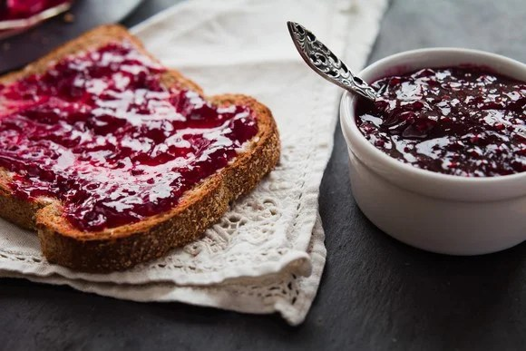A piece of jelly toast sits on a napkin next to a bowl of jelly.