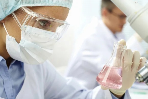A biotech lab tech examining a beaker of liquid.