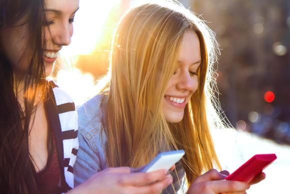 Millennials surfing Facebook on their smartphones.