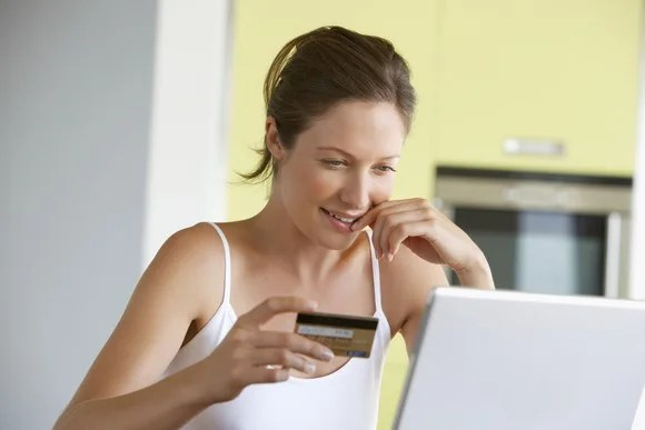 A woman holding a credit card and debating an online purchase.