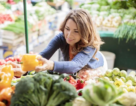 woman grabbing pepper in grocery aisle