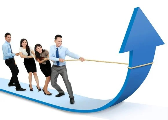 A diverse group of four businesspeople standing on a blue arrow, pulling a rope to make it point upward.