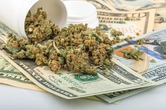 A tipped over bottle of cannabis buds on a pile of cash.