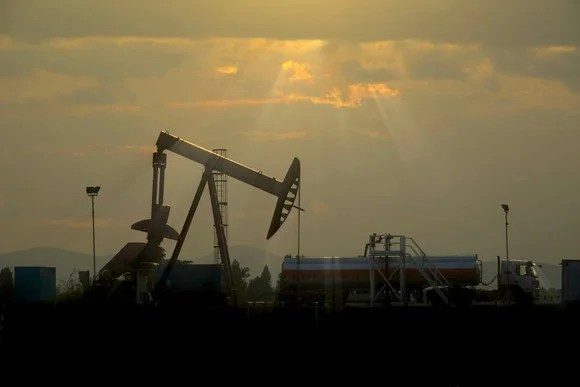 An oil pump with the sun breaking through behind the clouds in the background.