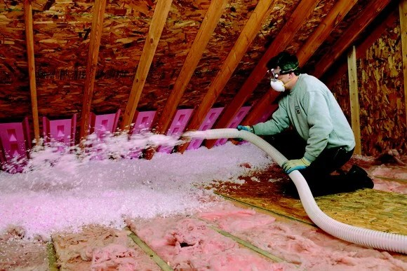 a man applying insulation to an attic
