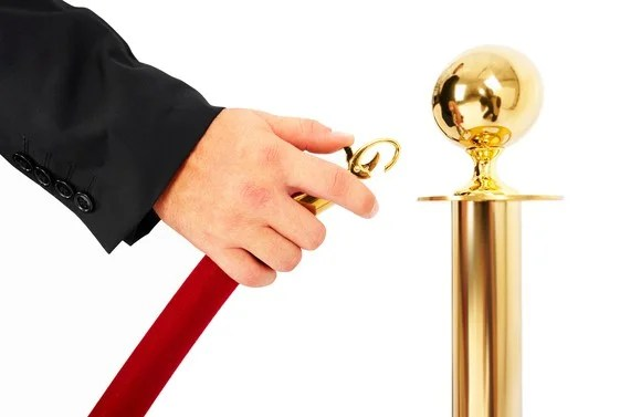 hand moving a red velvet rope aside to permit entry