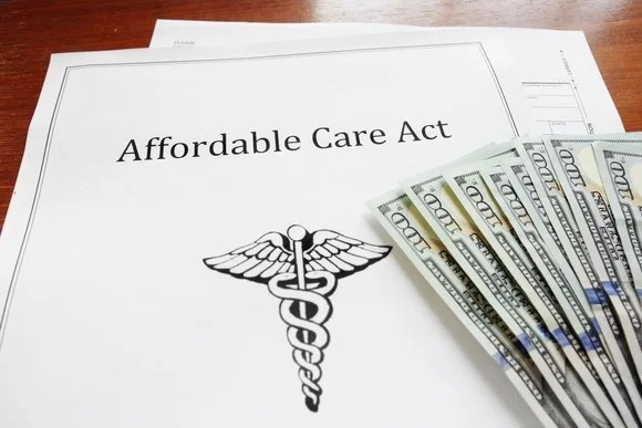 An Affordable Care Act plan with a fanned pile of hundred dollar bills lying on top.