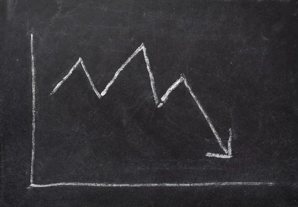 A chalkboard sketch of a stock chart showing a stock price falling