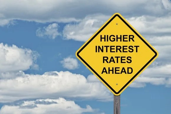 yellow road sign that says higher interest rates ahead