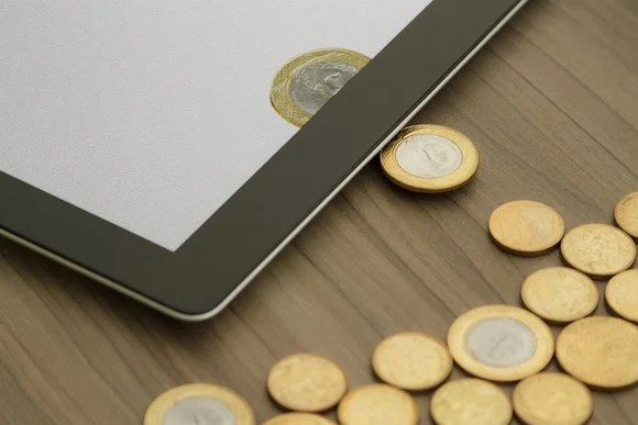 Physical coins being turned into digital coins on a tablet.