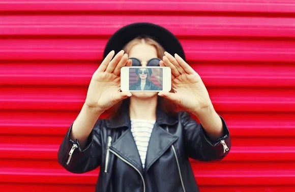 Fashionably dressed woman taking a selfie against a striking pink wall.