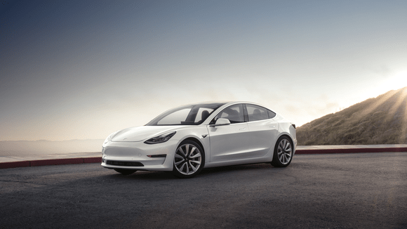White model 3 beside a mountain