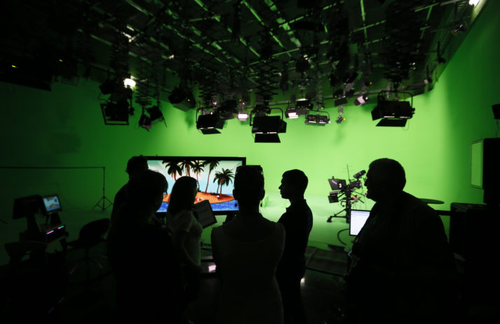 Employees of Russia Today wait for the arrival of President Vladimir Putin at network's studio complex in Moscow