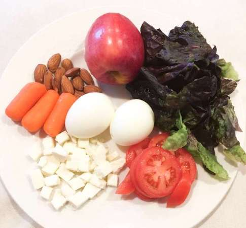last minute dinner idea - A plate of eggs, cheese, tomatoes, c carrots, almonds, apples, and lettuce