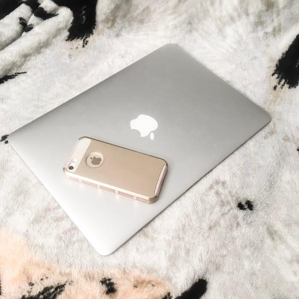 A MacBook with a computer lying on top