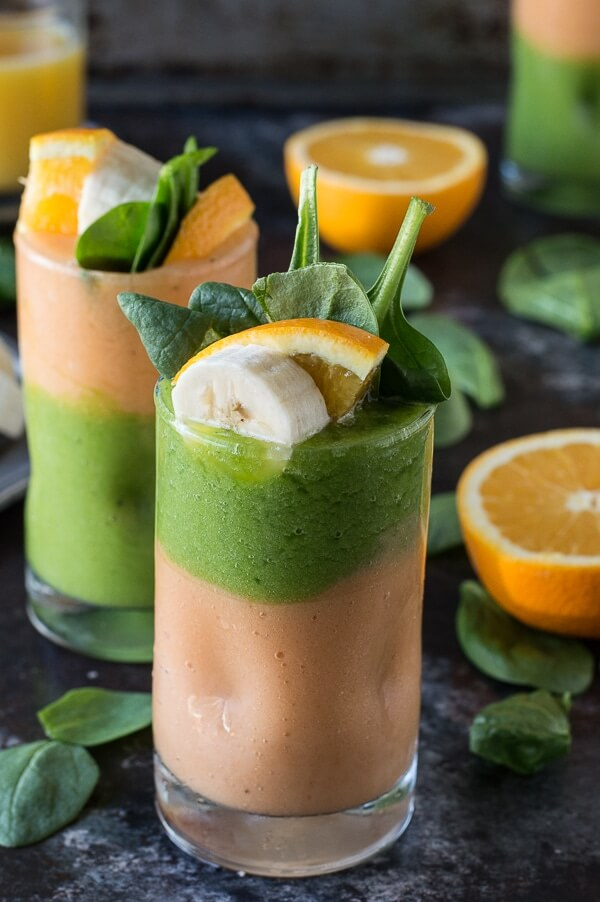 This is a orange and green post workout smoothie garnished with a slice of orange and spinach.