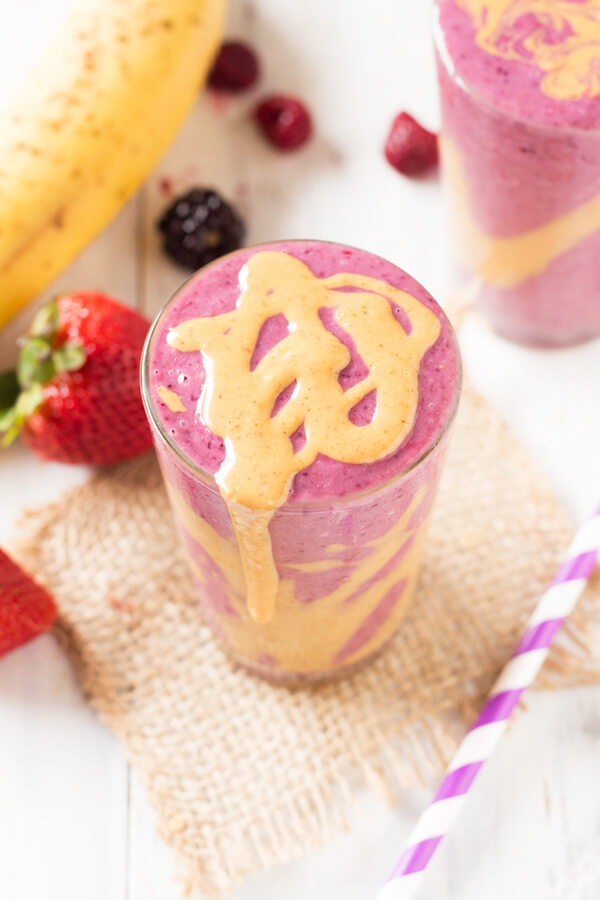 A pink berry post workout smoothie, topped with peanut butter.