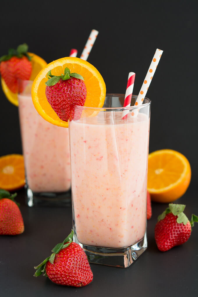 There are two strawberry smoothies on a table, garnished with a slice of orange and a strawberry.