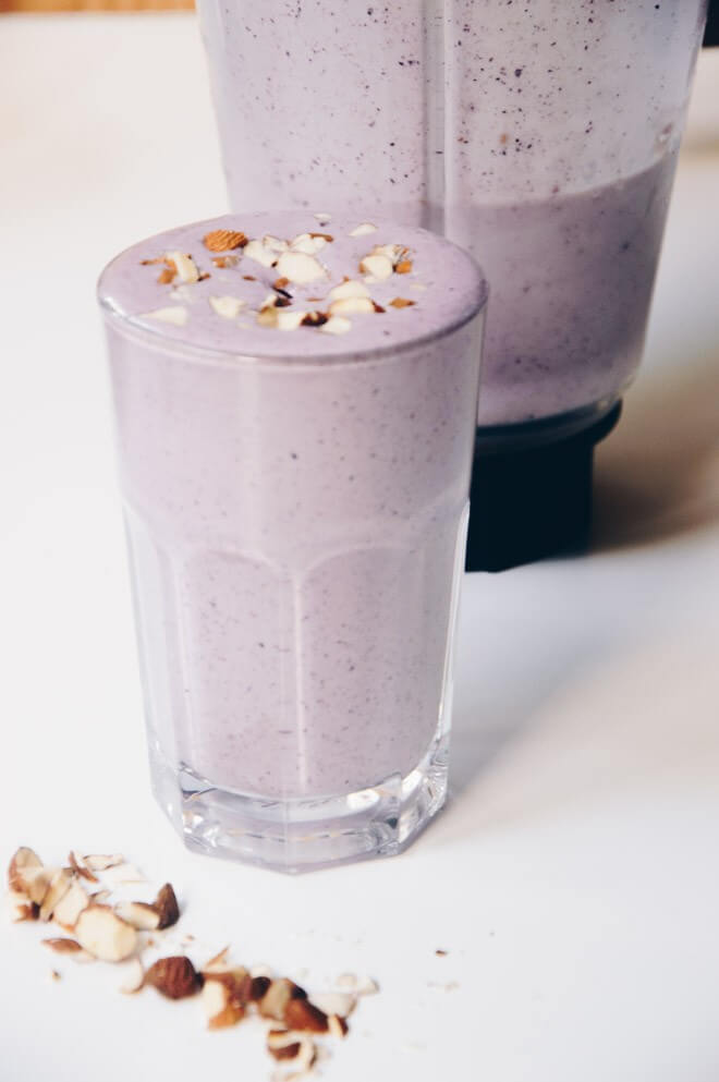 A purple berry smoothie topped with nuts.