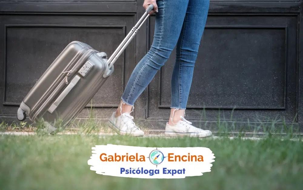 Afrontar la Culpa Expat en tu Vida en el Extranjero - Gabriela Encina - Psicologa Expat Online- Mujer expat caminando con una maleta