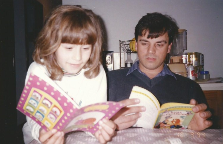 A girl and her dad sitting at the table, each one reading a book.