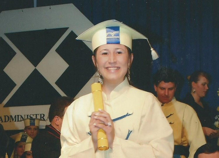 Young woman, wearing a graduation gown and cap, holding her diploma.