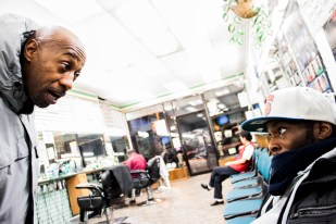 """Cory C., 35 is scolded by his friend """"A.B."""" for sitting in a barber shop without paying for something. Cory was trying to escape the cold. Photo by Gabrielle A. Wright."""