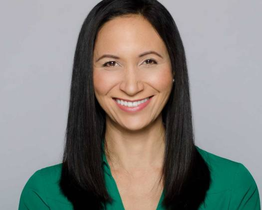 Professional business corporate headshot of woman in green shirt against grey backdrop