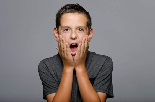 studio modeling test portrait of a young boy against a grey background
