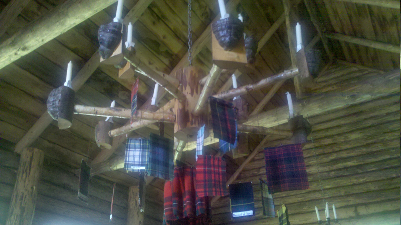 Log, tree fungus, and tartan chandelier in the Loch Broom Log Cabin Church