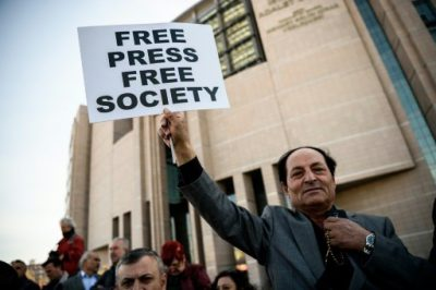 "© AFP/File | A demonstrator holds a placard reading ""Free Press Free Society"", outside the Istanbul courthouse on April 1, 2016"