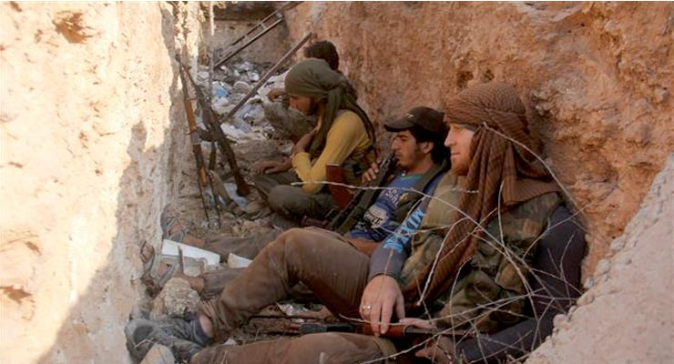 This picture taken on August 6, 2016 shows members of the Jabhat Fateh al-Sham terrorist group sitting in a trench in the northern Syrian city of Aleppo. ©AFP
