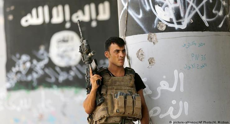 """A member of Iraqi counterterrorism forces stands guard near graffiti supportive of the """"Islamic State"""" after expelling the group from Fallujah"""