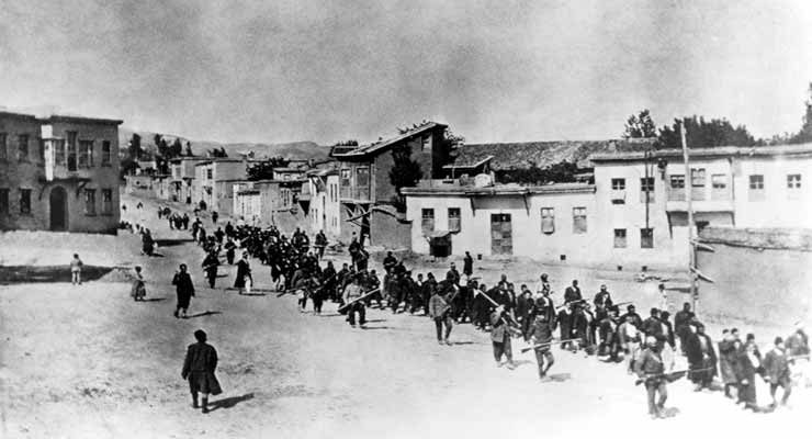 Armenian civilians, escorted by Ottoman soldiers, marched through Harput to a prison in nearby Mezireh (present-day Elazig), April 1915.