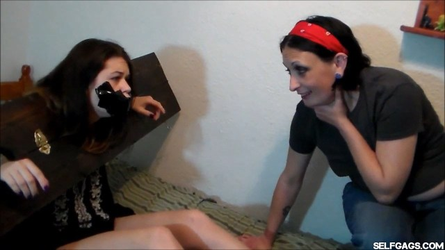 Young girl locked in stockade and tape gagged by woman selfgags