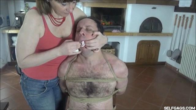 Woman stuffs dirty panties in man's mouth