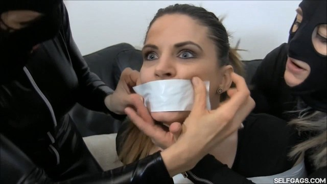 Girl with panties in her mouth is tape gagged by catsuit burglars selfgags