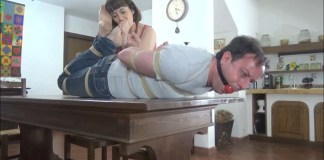 Woman licks male feet while he is hogtied and gagged on table