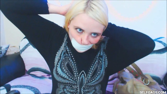 Blonde girl gags herself with microfoam tape around the head at selfgags.com