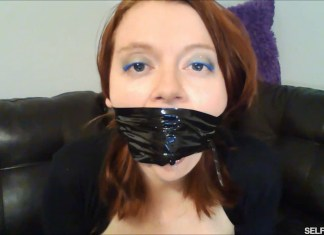 Redhead gagged with black bondage tape around the head