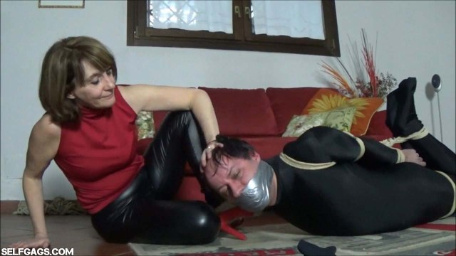 Tape gagged man hogtied by woman