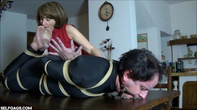 Woman sucks toes on bound and gagged man