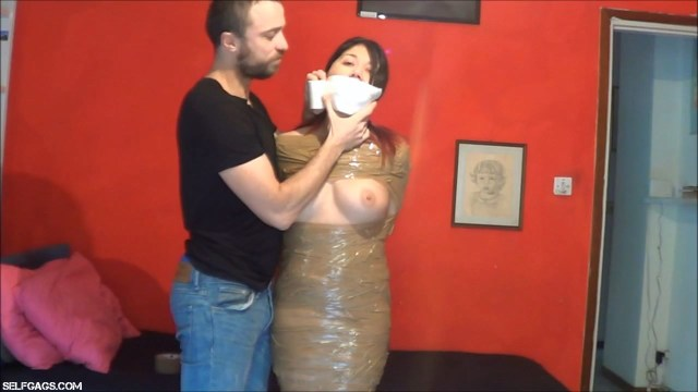 Girl with big tits gagged with microfoam tape in mummification bondage