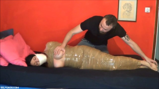 Girl with big tits tape gagged and wrapped in mummification bondage
