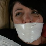 Girl with black hair gagged with white duct tape