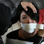 Girl with black hair wrap gagged with white duct tape by female in leather catsuit